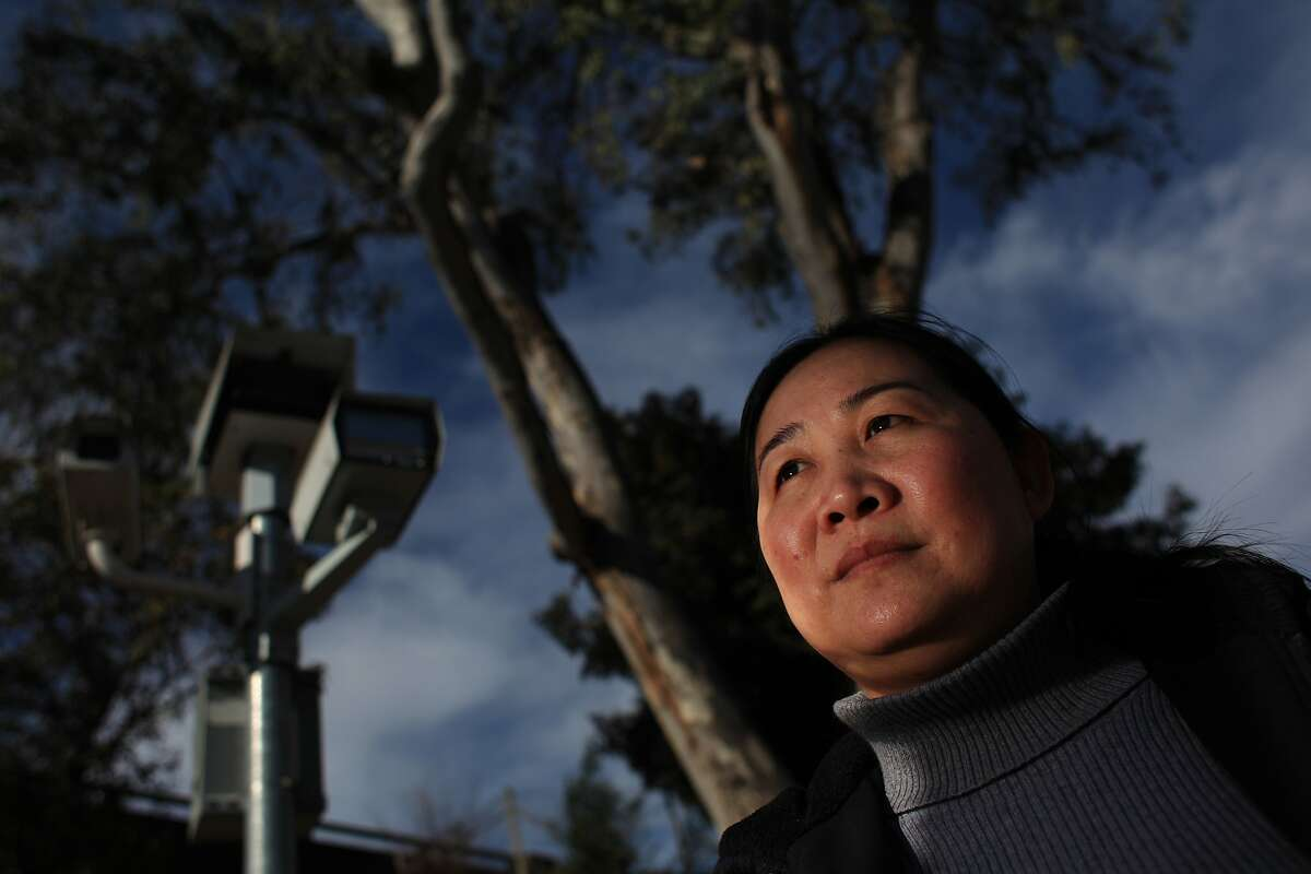 In this file photo, Phuong Nguyen of Oakland stands near a red light camera unit at the 27th St. on ramp to I-580 at Northgate Avenue in Oakland. Nguyen periodically works at her family's flower store, MP Flowers, on 27th Avenue and says 3 family members have gotten tickets at the corner.