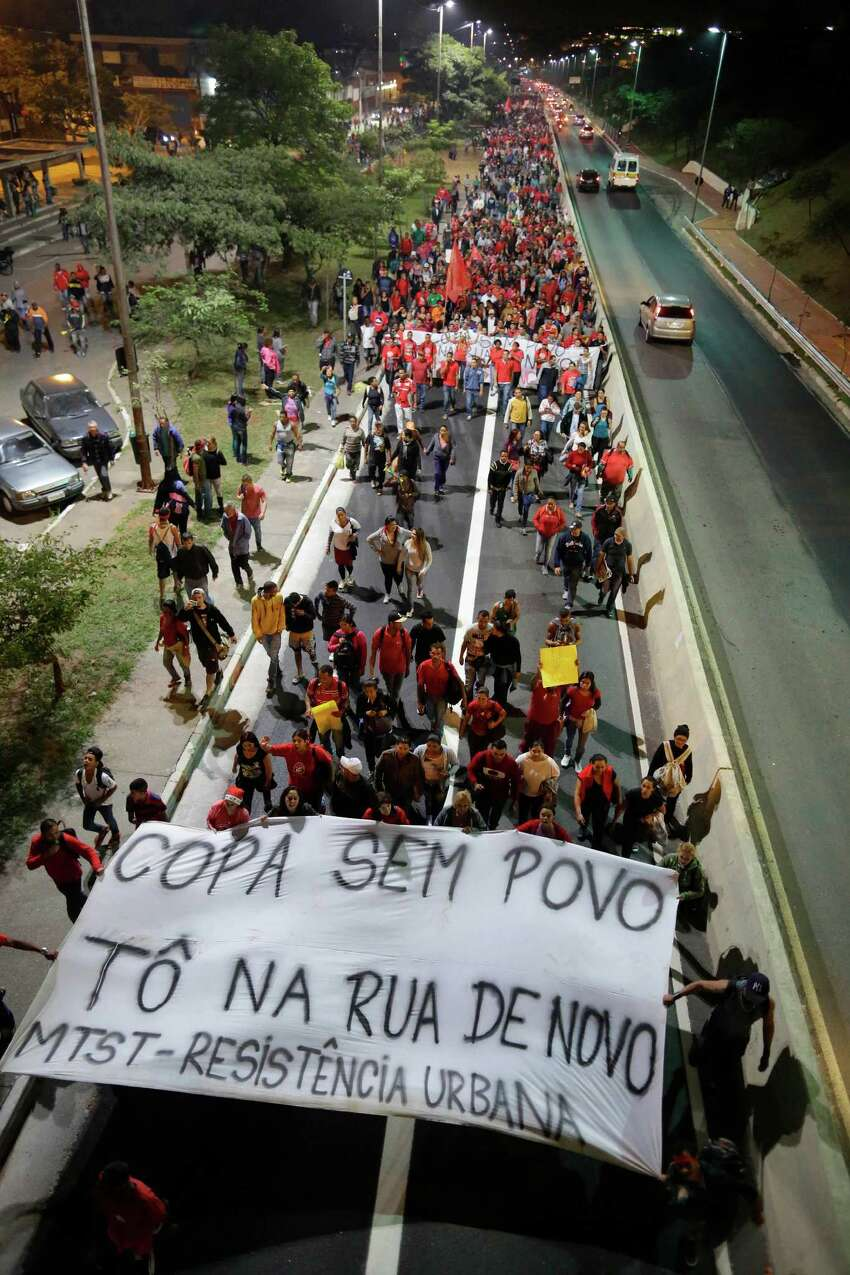 Members of the Homeless Workers Movement holding a banner that reads in Portuguese