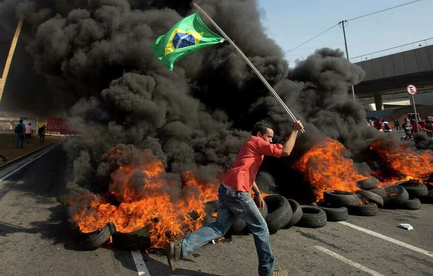 In this May 15, 2014 photo, a member of the Homeless Workers Movement carries a Brazilian flag past burning tires during a protest against the money spent on the World Cup near Itaquerao stadium which will host the international soccer tournament's first match in Sao Paulo, Brazil. Brazilians are angry at the billions spent to host the World Cup, much of it on 12 ornate football stadiums, one-third of which critics say will see little use after the big event. (AP Photo/Andre Penner,File)