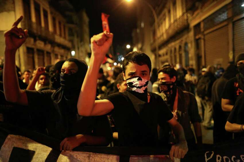 Masked demonstrators protest the World Cup in Rio de Janeiro, Brazil, Friday, May 30, 2014. Brazil has seen near-daily protests of late with anger focused on the billions spent to host next month's World Cup soccer tournament. (AP Photo/Leo Correa)