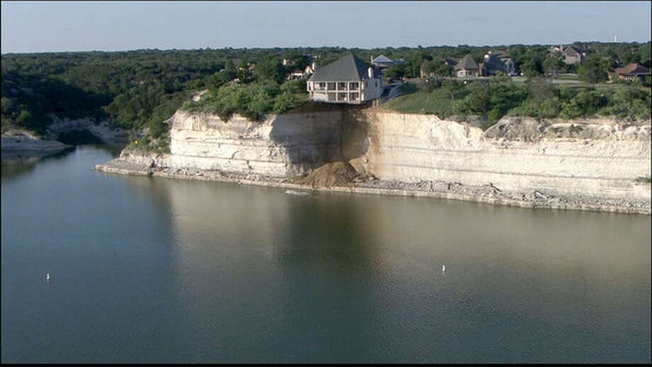 The edge of the 4,000 square foot residence on Overlook Court is dangling about 75 feet above the rocky shoreline after part of it had already broken off. Tax records show the residence, in the White Bluff Resort subdivision, was built in 2007 and is valued at more than $700,000. Photo: WFAA-TV