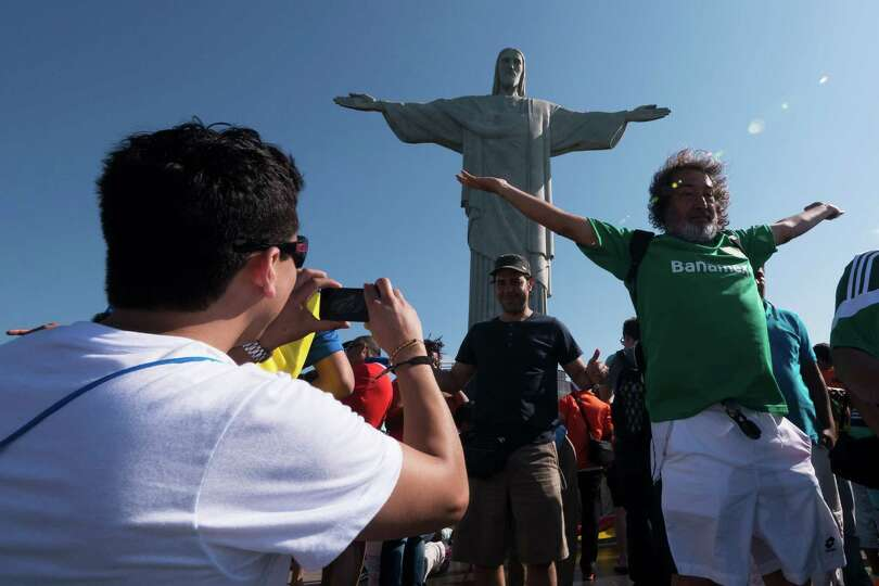 RIO DE JANEIRO, BRAZIL - JUNE 09:  Tourists pose for photos in front Christ the Redeemer statue prio