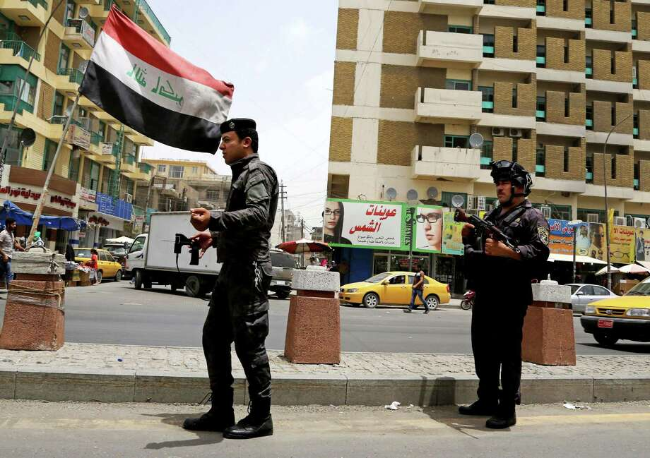 Iraqi federal policemen stand guard at a checkpoint in Baghdad, Iraq, Wednesday, June. 11, 2014. The Iraqi government has tightened its security measures after a stunning assault that exposed Iraq's eroding central authority, al-Qaida-inspired militants overran much of Mosul on Tuesday, seizing government buildings, pushing out security forces and capturing military vehicles as thousands of residents fled the Iraqi second-largest city. Photo: Karim Kadim, AP / AP