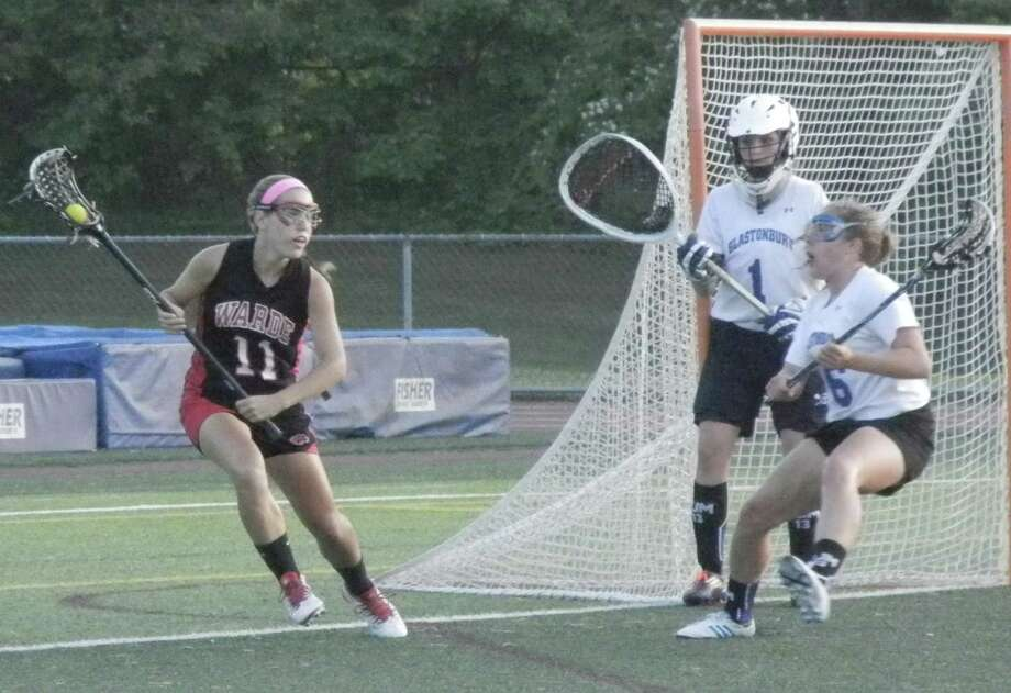 Sophomore attacker Amanda Orvis, of the Mustangs (11), considers trying to turn the corner near the Glastonbury goal on Tuesday, June 10 in a CIAC Class L girls lacrosse semifinal at West Haven's Ken Strong Stadium. Orvis had three of Warde's goals in a 13-5 loss to the Tomahawks. Audrey Apanovitch (1) is Glastonbury's goalie. Photo: Reid L. Walmark / Fairfield Citizen