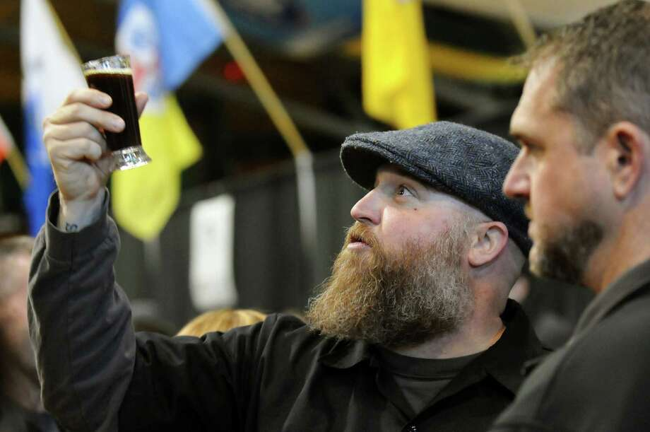 Kenny Comstock of Saratoga Springs, center, holds up a glass of Druthers Brewing Company's Fist of Karma as he looks at the color during the Albany Winter Brewfest on Saturday, Feb. 8, 2014, at the Washington Avenue Armory in Albany, N.Y. Joining him is Randy Schon of Malta, right. (Cindy Schultz / Times Union) ORG XMIT: MER2014020816453591 Photo: Cindy Schultz / 00025607A