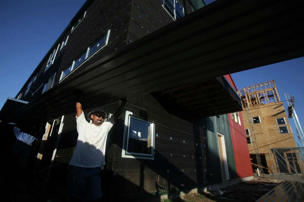New construction: In recent years, 475 townhomes and 240 luxury apartment lofts have gone up, according to the Greater East End Management District. Jose Hernandez joins a work crew building new town homes along Commerce St. in the Second Ward on June 5, 2014.