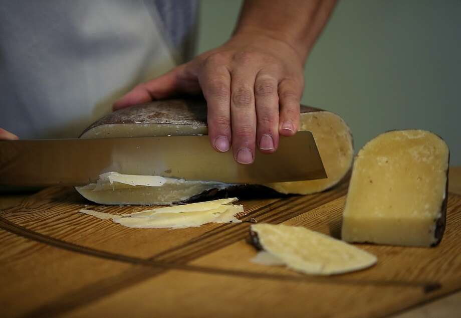 Cheese maker Gabriel Luddy cuts a wheel of dry aged Jack cheese at Vella Cheese in Sonoma. Photo: Justin Sullivan, Getty Images