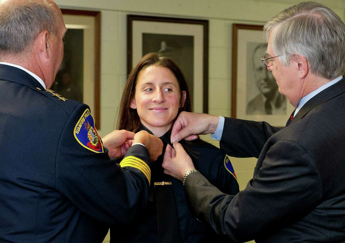 Stamford Police Chief Jon Fontneau, left, and Stamford Mayor David Martin, right, pin bars on Kelly Connelly's uniform during a ceremony to swear in new police sergeants Wednesday at police headquarters in Stamford, Conn., on June 11, 2014.