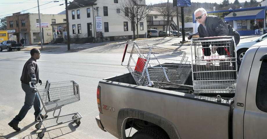 Matt Reed, with the Danbury Park and Rec department left and Tom Vecchiarino , with the Highway Department, load shopping carts into a city truck that they have found around the downtown area. About once a week, city workers drive around looking for carts taken from grocery stores and left around town. Photo: Carol Kaliff / The News-Times