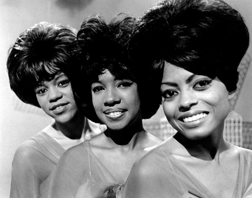"""The Supremes originally started in 1959 as a foursome called The Primettes, a sister act to the male-centric group, The Primes, which featured Pail Williams and Eddie Kendricks of the Temptations. When the group signed on with Motown Records in 1960, Betty McGlown, who sang with Diana Ross, Mary Wilson, and Florence Ballard in the Primettes, dropped from the group, and Barbera Martin filled the vacancy. However, about two years after the Motown Records deal, Martin dropped from the group, leaving the trio you're probably most familiar with. Hit songs by the Supremes include, """"Baby Love"""" (1964), """"Come See About Me"""" (1965), and """"Stop! In the Name of Love"""" (1965). The from left to right, Florence Ballard, Mary Wilson and Diana Ross pose for a photo for an episode of the British television show, Thank Your Lucky Stars in October of 1964. Photo: David Farrell, Getty / Redferns"""