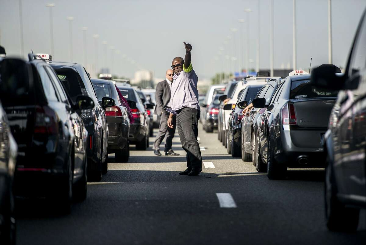 TOPSHOTS Taxis drivers block highway outside Paris, near Roissy on June 11, 2014, as they take part in a demonstration to protest against the growing number of minicabs, known in France as Voitures de Tourisme avec Chauffeurs (VTC). Taxi drivers in London, Paris and other European capitals plan to bring chaos to the streets Wednesday in protest against unlicensed mobile car-hailing services such as Uber which have shaken up the industry. AFP PHOTO / FRED DUFOURFRED DUFOUR/AFP/Getty Images