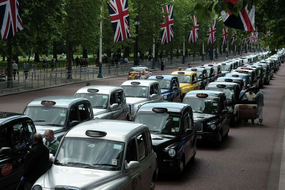 Parked taxis block the Mall leading to Buckingham Palace during a protest by London black cab drivers against Uber in central London on June 11, 2014. Taxi drivers brought parts of London, Paris and other European cities to a standstill on June 11 as they protested against new private cab apps such as Uber which have shaken up the industry. Photo: CARL COURT, Getty Images / AFP