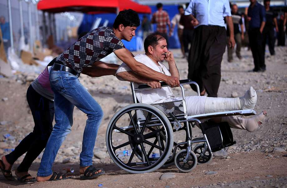 An Iraqi man in a wheelchair fleeing violence in northern Nineveh province arrives at a checkpoint in the autonomous Kurdistan region. As many as half a million people have fled their homes. Photo: Safin Hamed, AFP/Getty Images
