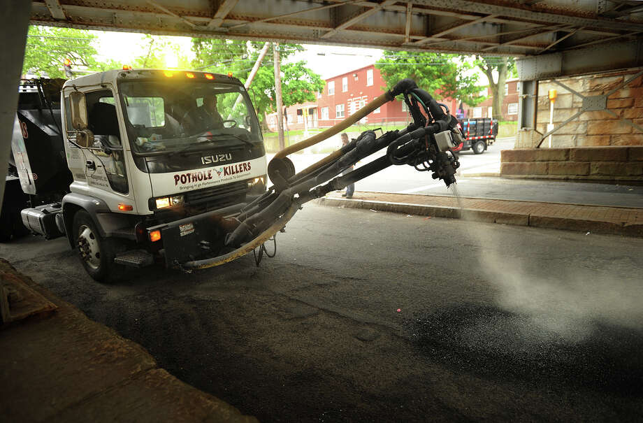 The Pothole Killer, a pothole repair vehicle being leased by the city of Bridgeport, fills a pothole beneath the Park Avenue train overpass in Bridgeport, Conn. on Wednesday, June 11, 2014. Photo: Brian A. Pounds / Connecticut Post
