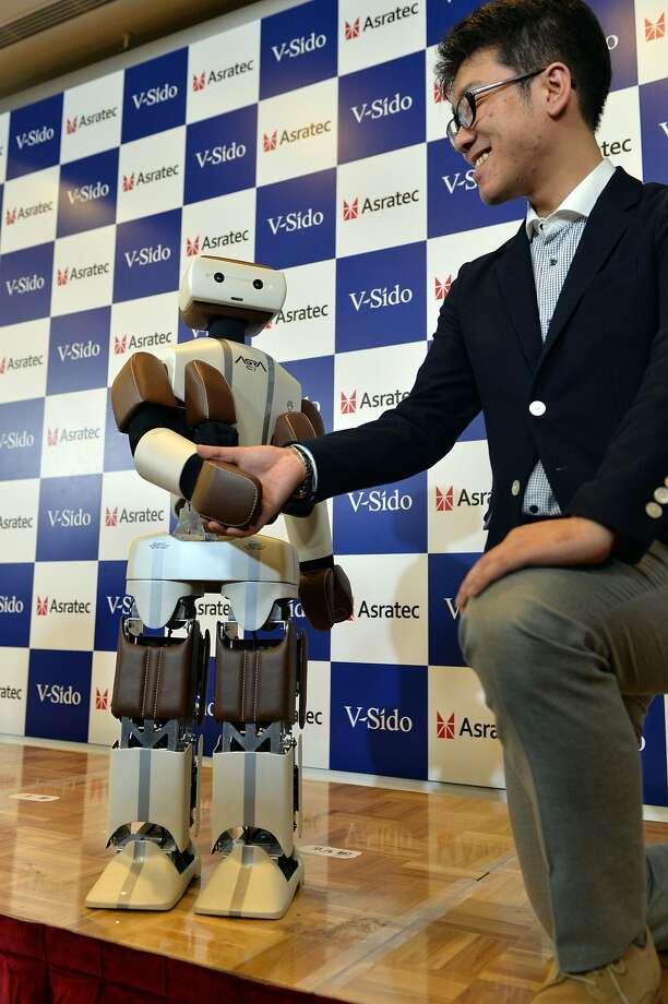 Very good, Asra! You can let go now .... Asra, release my hand ... Asra?  Robotics engineer Wataru Yoshizaki shakes hands with Asra C1 while demonstrating its abilities at Asratec, a subsidiary of Japanese telecommunication giant Softbank in Tokyo. The robot is scheduled to go on sale this year. Photo: Yoshikazu Tsuno, AFP/Getty Images
