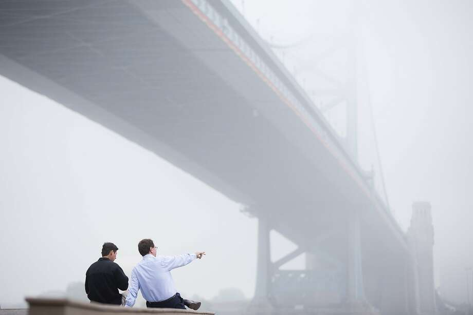 Under Ben's bridge: Two men take in the view of the fog-veiled Benjamin Franklin Bridge at the Race Street Pier in Philadelphia. Photo: Matt Rourke, Associated Press