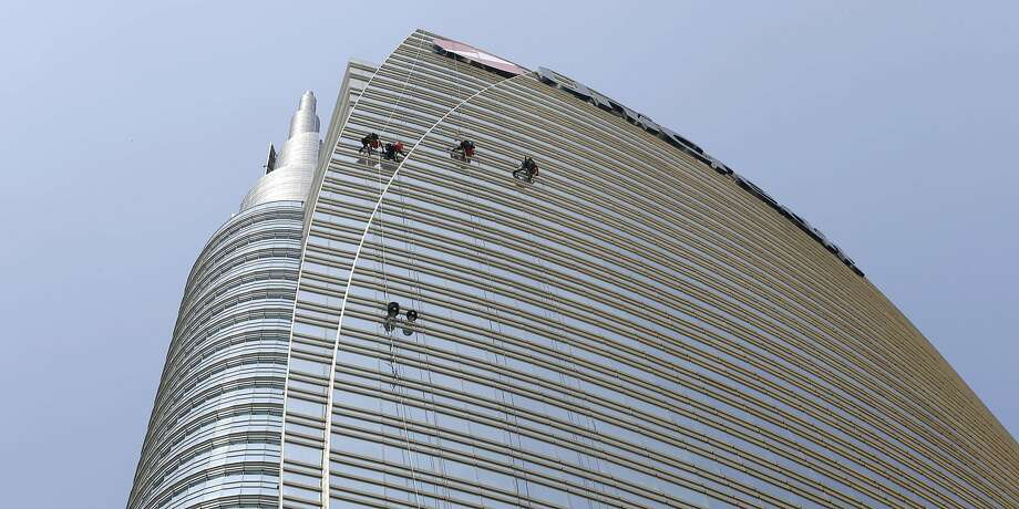Window cleaners dangle from ropes on the side of the Unicredit tower at Piazza Gae Aulenti in Milan. The Unicredit Tower, the shiny new headquarters of Italy's largest bank, has claimed the title of Milan's tallest building at 218 meters (715 feet). Photo: Luca Bruno, Associated Press