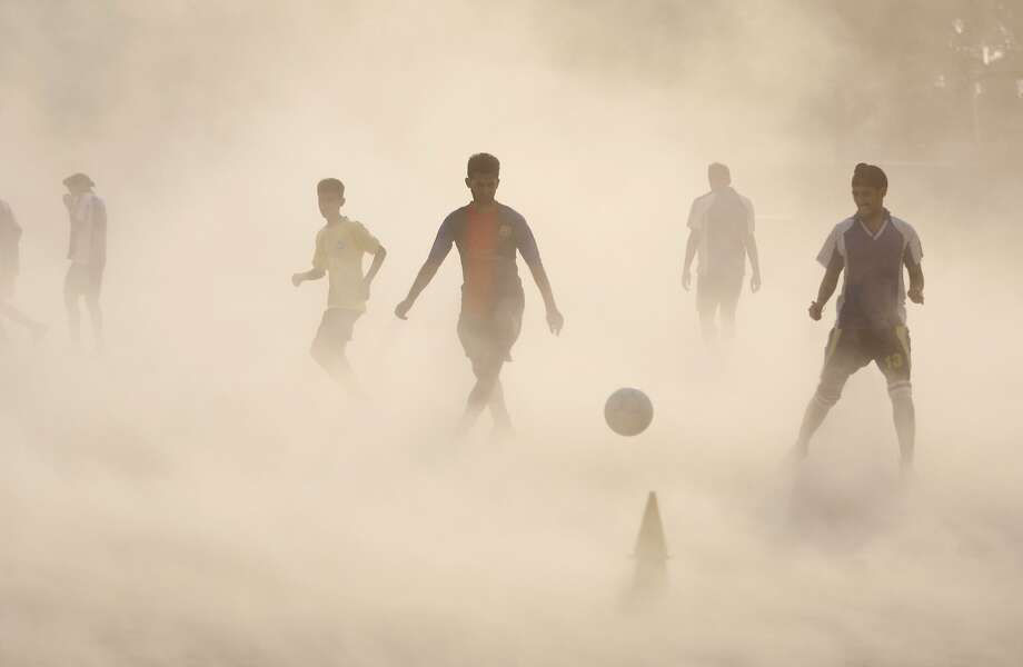 Now if we can only find the goal ...Despite a dust storm choking their throats and blinding their eyes, young Indian soccer players keep practicing in Jammu. Photo: Channi Anand, Associated Press