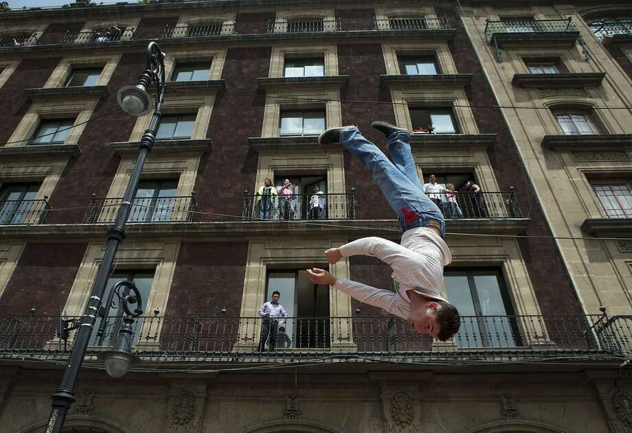 Not a defenestration:He's actually doing flips on an unseen trampoline, not tumbling off the building. Acrobats, clowns and other circus performers rallied in Mexico City to protest the city's new ban on circus animals. Photo: Rebecca Blackwell, Associated Press