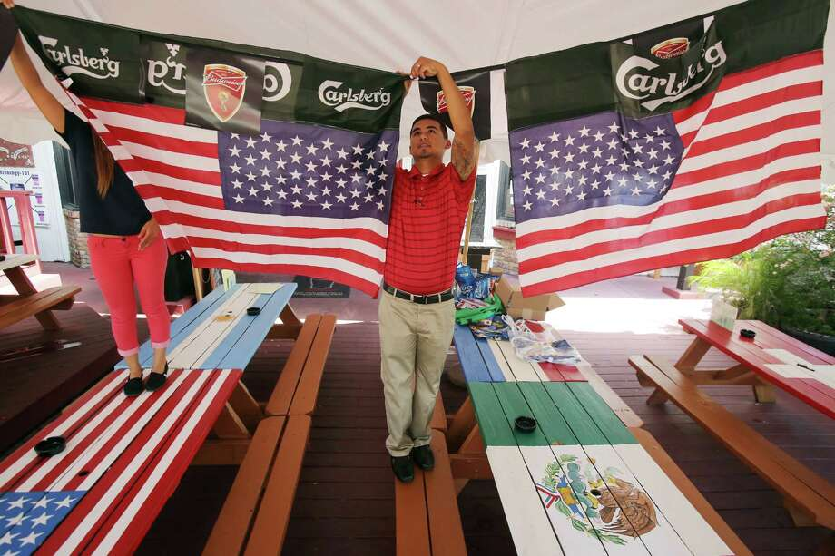 Romero Fuentes, 26, helps decorate the patio area for Richmond Arms Pub as it prepares for World Cup viewing parties on June 11, 2014, in Richmond, Tx. Photo: Mayra Beltran, Houston Chronicle / © 2014 Houston Chronicle