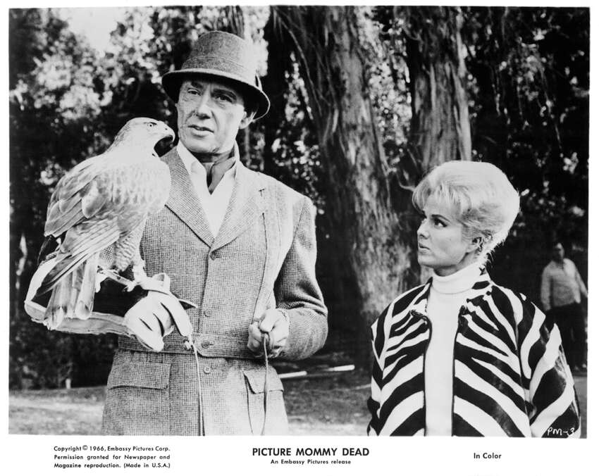 Maxwell Reed holds a falcon with Martha Hyer in a scene from the film