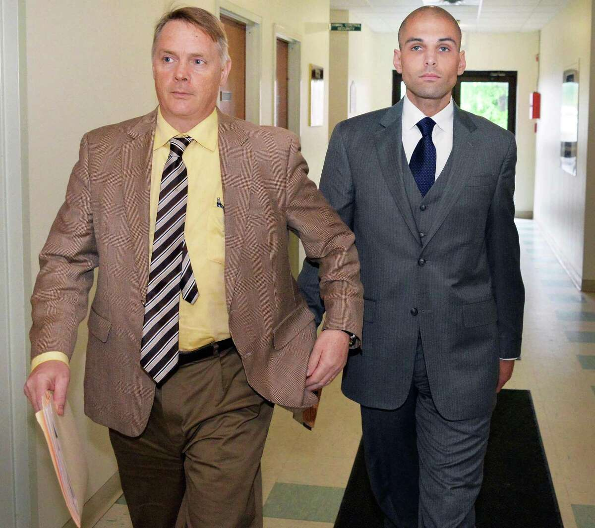 The Rev. James Michael Taylor, right, an associate pastor at St. Kateri Tekakwitha Parish in Niskayuna, arrives at Clifton Park Town Court Wednesday afternoon, June 11, 2014, in Clifton Park, N.Y. Taylor is accused of engaging in physical contact and sharing phone calls, text messages and pictures with a 15-year-old girl he met while serving as a deacon and youth minister at Corpus Christi Church in Clifton Park. (John Carl D'Annibale / Times Union)