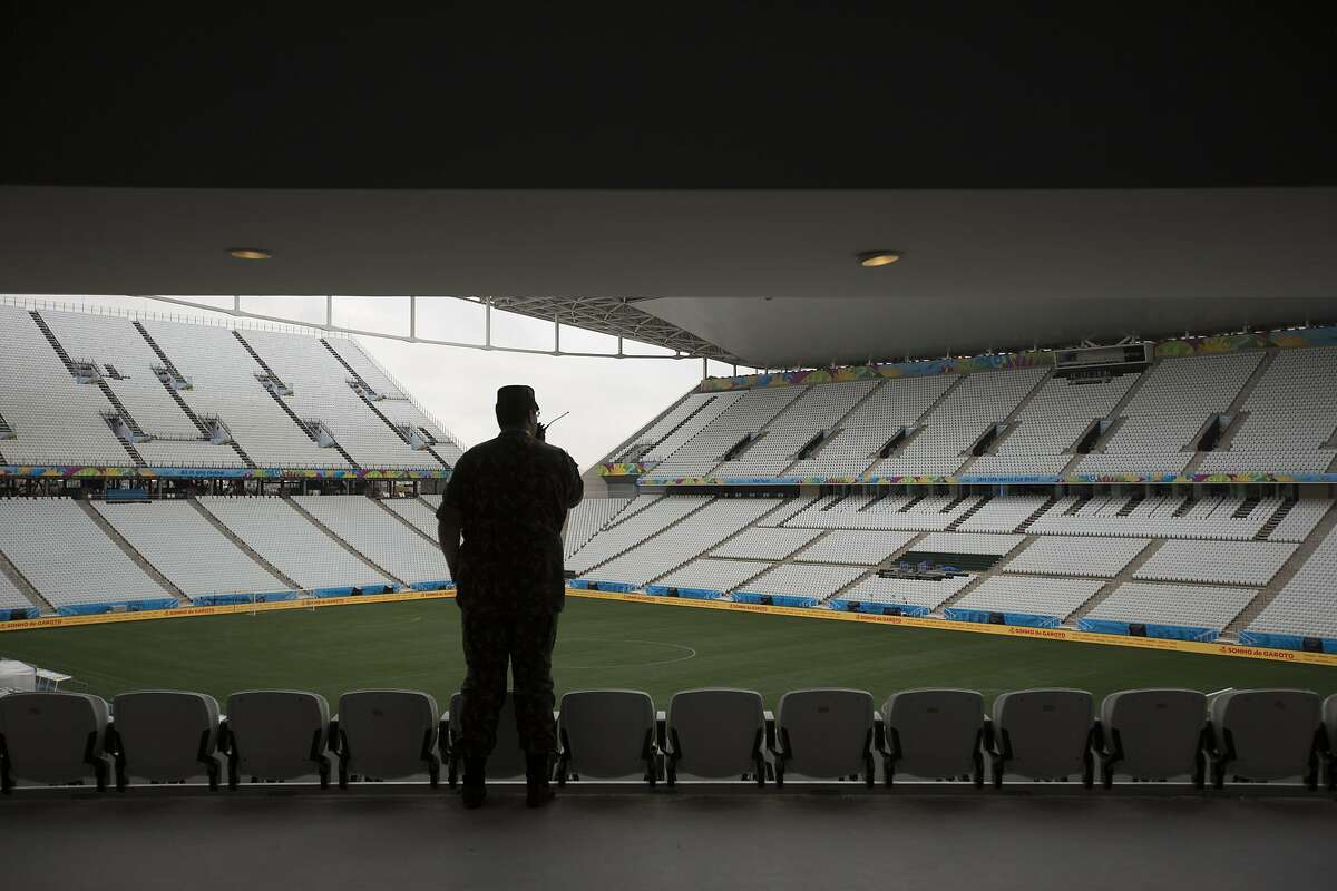 A soldier talks on his radio as he overlooks Itaquerao Stadium one day before the opening World Cup soccer match in Sao Paulo, Brazil, Wednesday, June 11, 2014. If Brazil wins the opening game, the fact that Itaquerao stadium isn't even fully finished yet will quickly be forgotten. (AP Photo/Felipe Dana)