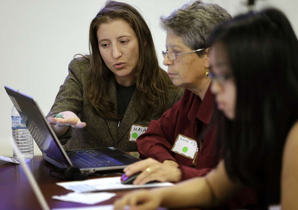 In this Tuesday, Oct. 15, 2013 photo, Maia Weinstock, of Cambridge, Mass., left, a Brown University graduate, works with Anne Fausto-Sterling, of Cranston, R.I., center, a professor of biology and gender studies, during a Wikipedia