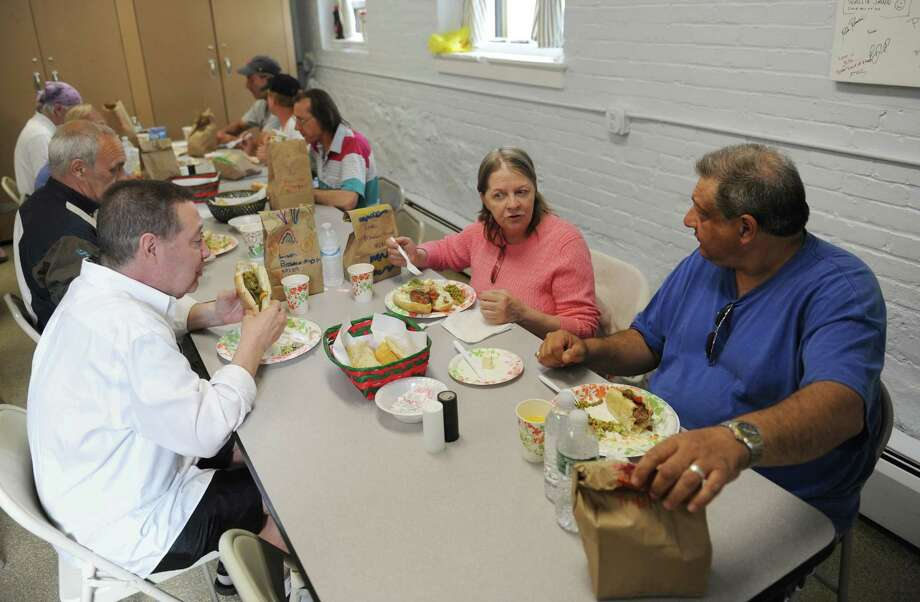 New Milford residents John Frank, left, Elizabeth Pyron, and Lou Perna, Sr. eat dinner at Loaves & Fishes Hospitality in New Milford, Conn. Wednesday, May 21, 2014.  The pantry feeds the hungry in New Milford and typically gives out between 25 and 30 meals per day.  Loaves & Fishes is entirely volunteer-run and gives out donated food with no state or federal funding. Photo: Tyler Sizemore / The News-Times