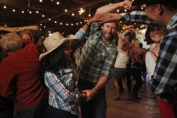 "From left, Birza Santiago, 26, Brian Boyce, 30, Stacey Garcia, 31, and Jesus Jocobo, 37, laugh as they do a group dance move together during the monthly barn dance May 17, 2014 at Pie Ranch in Pescadero, Calif. Every month, the educational farm holds a work day and welcomes people to volunteer at the farm. Afterwards, people gather for a potluck and then an evening of traditional barn dancing with a caller and a live band. Margaret More has been attending the dance for eight years, she says she enjoys the intergenerational aspect and added, ""it feels like [we've] stepped back 150 years in civilization."""
