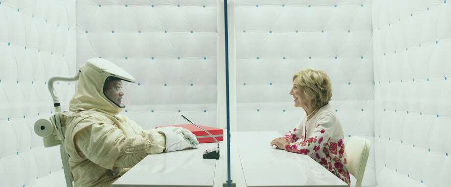 """Laurence Fishburne (left) as Dr. Wallace Damon, dressed in a contamination suit in an all-white hospital environment, and Lin Shaye plays Mirabelle in """"The Signal."""" Photo: Focus Features"""