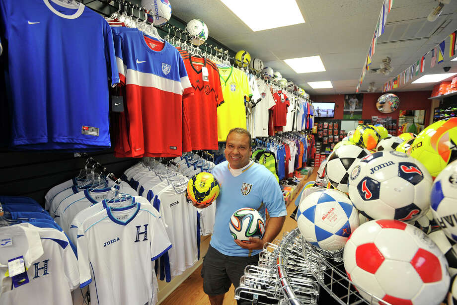 Owner Maynor Gonzalez poses among jerseys and soccer balls in his store Soccer Land on Summer Street in Stamford, Conn., on Wednesday, June 11, 2014. On Saturday at 4 p.m. Gonzalez plans on hosting a soccer player trading card party for all ages. Photo: Jason Rearick / Stamford Advocate