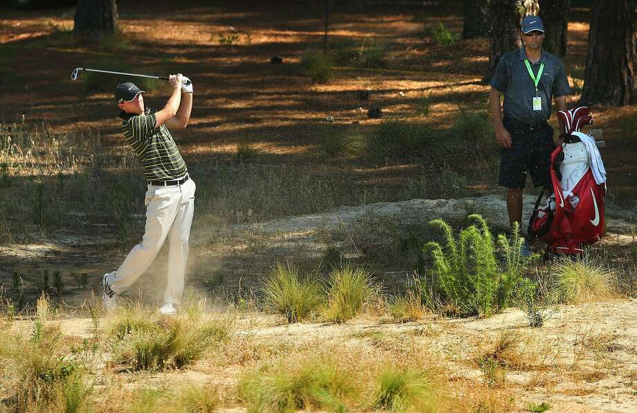 Russell Henley hits from one of Pinehurst No. 2's sandy waste areas. Forty acres of lush Bermuda-grass rough were removed from the course. Photo: Mike Ehrmann, Getty Images