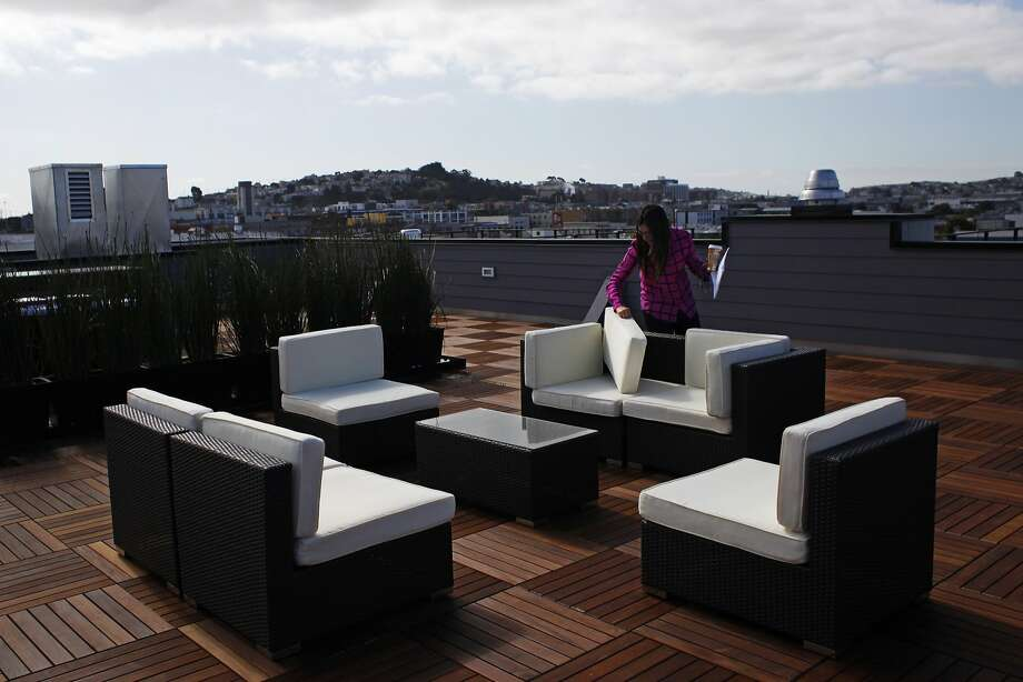 Rachel Turner, project manager of the 1515 15th St. residential development, adjusts furnishings on the building's roof deck during a media tour. It's in a part of the Mission District that's becoming a hot spot. Photo: Pete Kiehart, The Chronicle