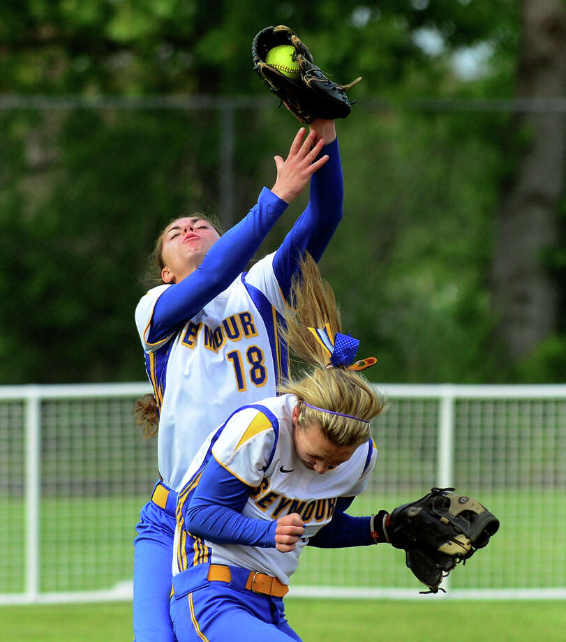 Seymour's Laura Dieckman narrowly misses colliding with teammate Katie Petroski, as Petroski catches a pop-fly, during Class M softball Semi-final action against Rocky Hill in Stratford, Conn. on Wednesday June 10, 2014. Photo: Christian Abraham / Connecticut Post