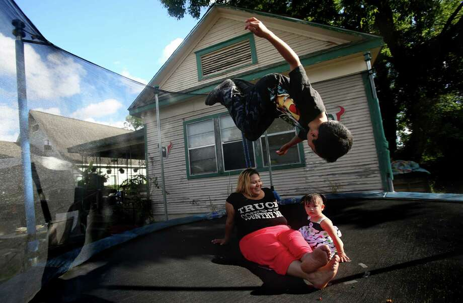 David Perez, 9, jumps on the trampoline while mother Amanda Ramirez and step-daughter Aleha Perez, 1, enjoy the breezy afternoon outside their home in the Second Ward on June 5, 2014, in Houston, Tx.  Amanda Ramirez grew up in this home near Rusk Park, and her family have lived in the Second Ward for decades. Photo: Mayra Beltran, Houston Chronicle / © 2014 Houston Chronicle