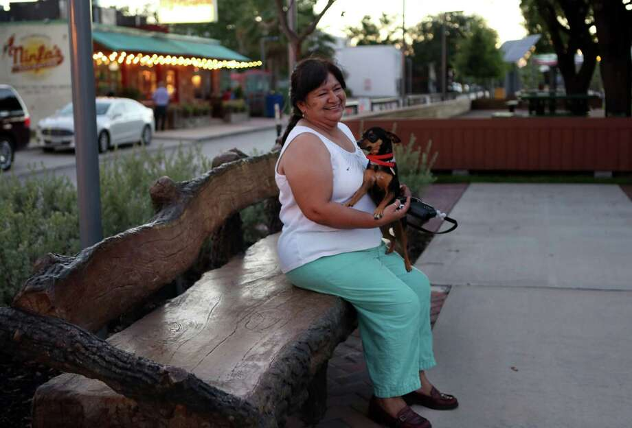 """Guadalupe Hernandez pets her dog """"Chiquis"""" after walking along the new Esplanade on Navigation in the Second Ward on June 5, 2014, in Houston, Tx. Photo: Mayra Beltran, Houston Chronicle / © 2014 Houston Chronicle"""