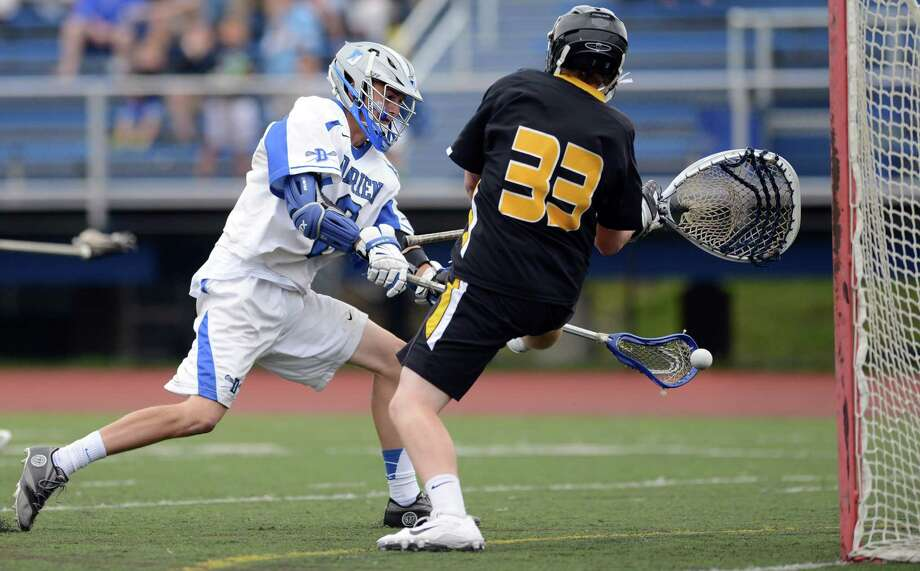 Darien's Peter Lindley gets the ball past Daniel Hand goalie Patrick Burkinshaw during the Class M lacrosse semifinals Wednesday, June 11, 2014, at Fairfield Ludlowe High in Fairfield, Conn. Photo: Autumn Driscoll / Connecticut Post