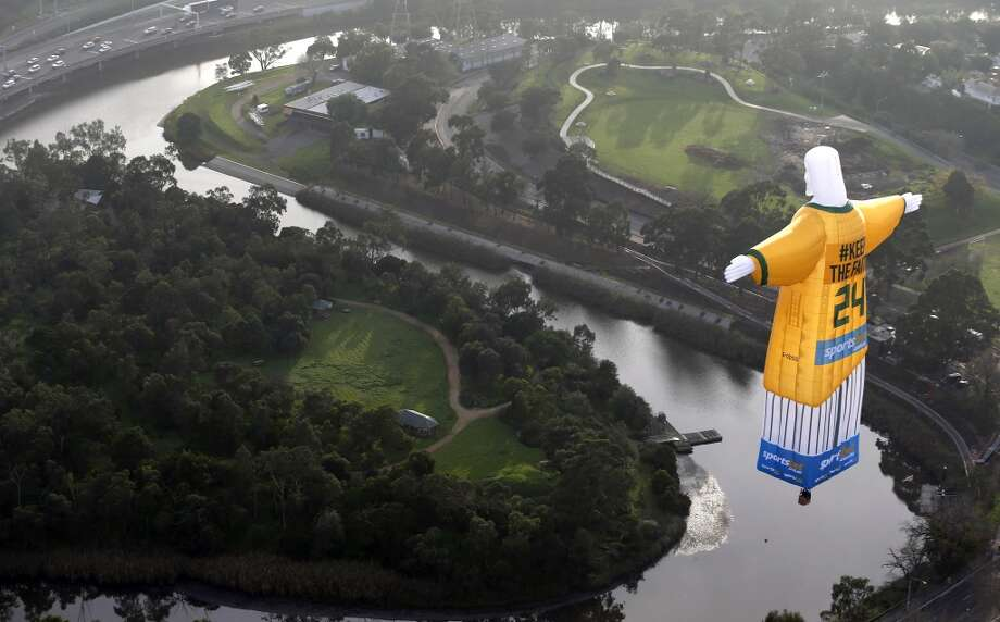 In this photo provided sportsbet.com.au, a hot air balloon in the likeness of Brazil's Christ The Redeemer statute, wearing the colors of Australia's soccer team floats over the Melbourne skyline Tuesday, June 10, 2014. Australia will begin their 2014 soccer World Cup campaign with a match against Chile Saturday, in Cuiaba. (AP Photo/sportsbet.com.au, Dave Callow) Photo: David Callow, Associated Press