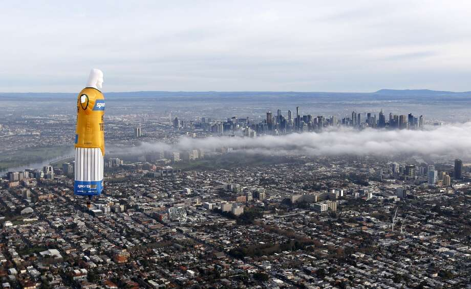 In this photo released by sportsbet.com.au, a hot air balloon in the likeness of Brazil's Christ The Redeemer statute, wearing the colors of Australia's soccer team, floats over the Melbourne skyline Tuesday, June 10, 2014. Australia will begin their 2014 soccer World Cup campaign with a match against Chile, Saturday, in Cuiaba. (AP Photo/sportsbet.com.au, Dave Callow) Photo: David Callow, Associated Press