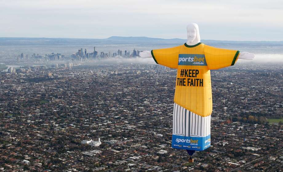 This handout photo taken and received on June 10, 2014 by Sportsbet.com.au shows a giant hot air balloon in the shape of Brazils Christ The Redeemer statue in an Australian football jersey flying over the Melbourne skyline in support of the Australian team ahead of the 2014 World Cup in Brazil.  The Australian team are preparing for their first game against Chile in the World Cup finals in Brazil which will be played on June 14. Photo: DAVID CALLOW, AFP/Getty Images