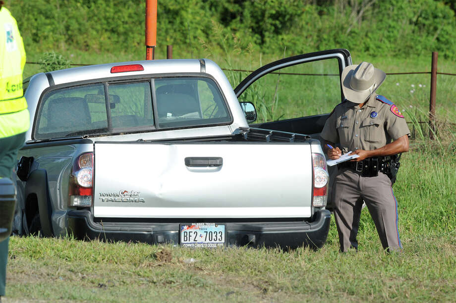A Texas State Trooper examines a pick up after a car accident Wednesday that killed an 80 year old man and hospitalized another man. The accident occurred on U.S. 90 around 5 p.m. Photo taken Wednesday, June 11, 2014 Guiseppe Barranco/@spotnewsshooter Photo: Guiseppe Barranco, Photo Editor