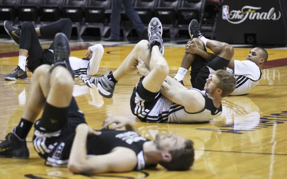 Spurs' Patty Mills (from right), Matt Bonner and Tiago Splitter stretch during practice and media sessions at the American Airlines Arena in Miami on Wednesday, June 11, 2014. (Kin Man Hui/San Antonio Express-News) Photo: San Antonio Express-News