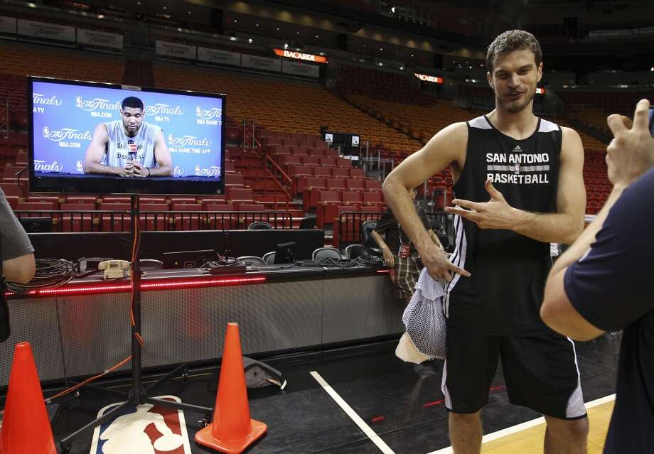 Spurs' Tiago Splitter (22) answers questions while teammate Tim Duncan talks to media in the conference room during practice and media sessions at the American Airlines Arena in Miami on Wednesday, June 11, 2014. (Kin Man Hui/San Antonio Express-News) Photo: San Antonio Express-News