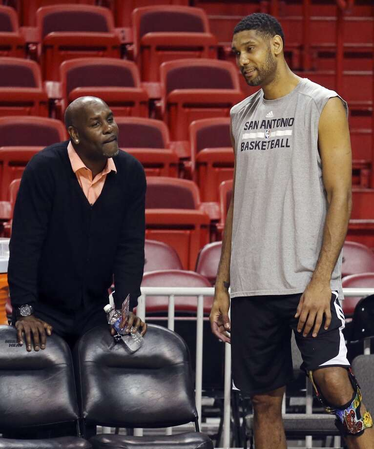 Former Seattle SuperSonics player Gary Payton (left) talks with San Antonio Spurs' Tim Duncan during practice Wednesday June 11, 2014 at American Airlines Arena in Miami, Fla. Photo: San Antonio Express-News