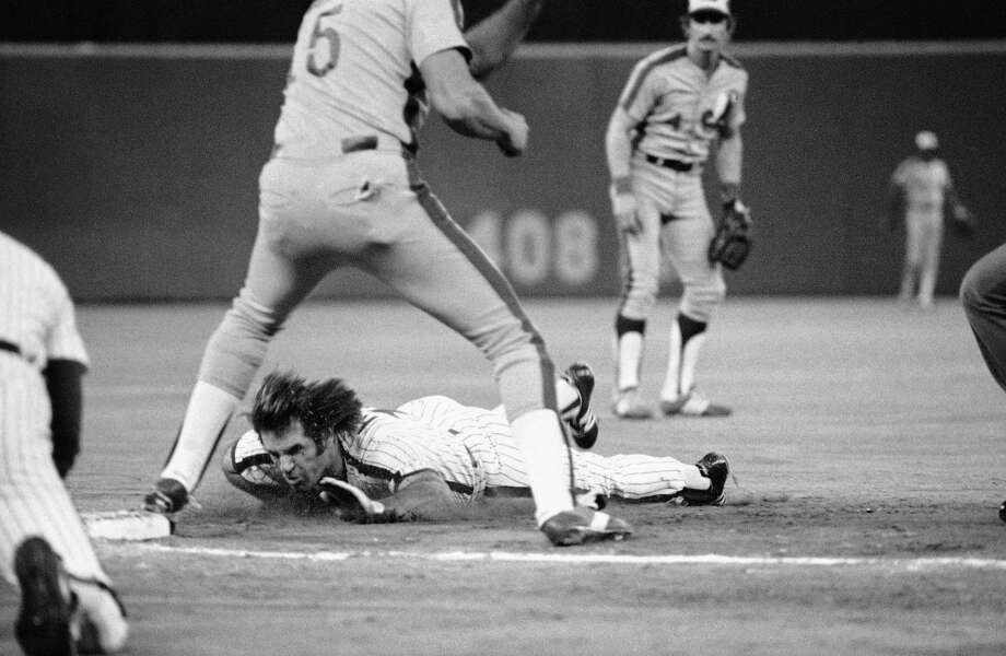 FILE - In this Sept. 8, 1981, file photo, Pete Rose, bottom, dives safely into third on a sacrifice by teammate Gary Matthews during early action against the Montreal Expos in Philadelphia, Pa. If Rose played today, his signature dives wouldn't be much of a novelty. It's become common in the majors for runners to fling their arms out, lead with their faces and hurtle toward bases. (AP Photo/Clem Murray, File) ORG XMIT: NY157 Photo: Clem Murray / AP