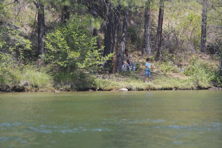 Son shows dad (seated) how it's done on shore of Lewiston Lake Photo: Tom Stienstra