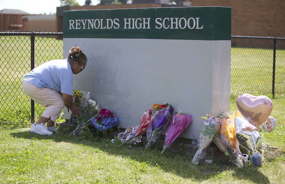 Fei Wilkening leaves flowers at a growing memorial outside Reynolds High School, site of Tuesday's shooting. Photo: Randy L. Rasmussen, Associated Press