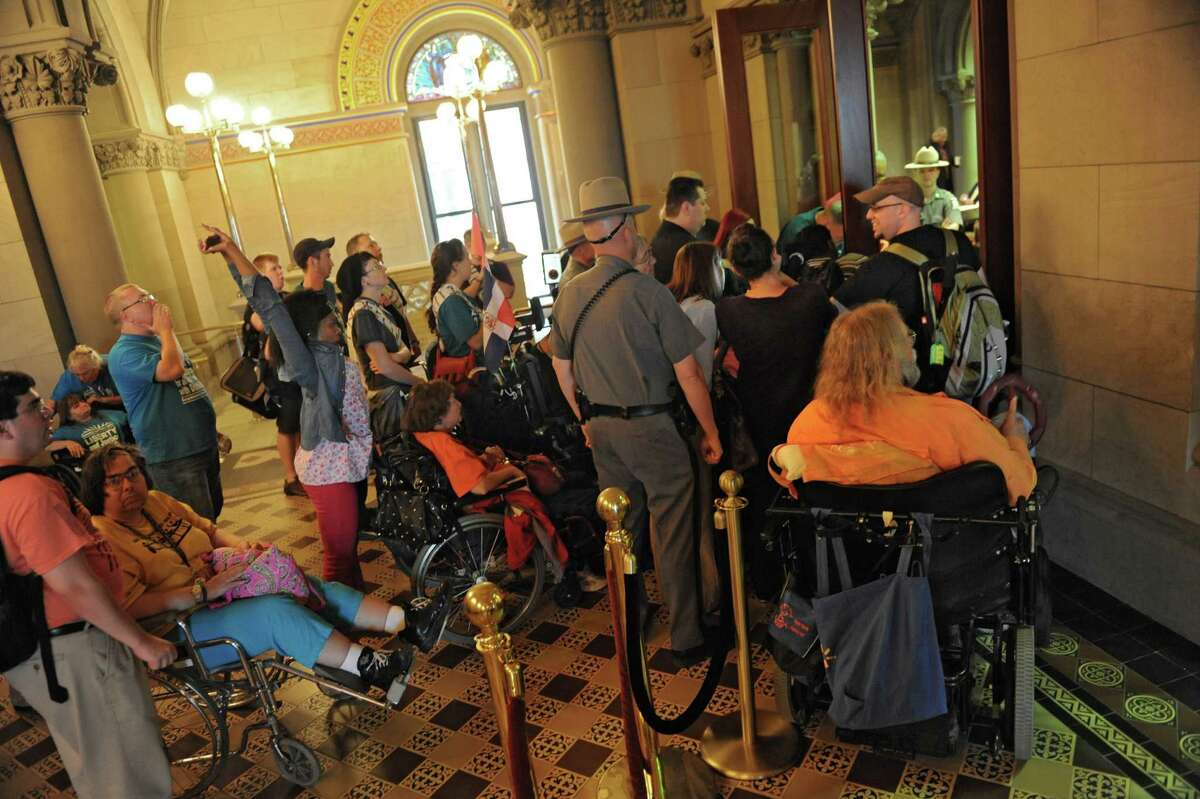 A group advocating to expand the range of home care options for the disabled, block a doorway to the Assembly Chamber Wednesday, June 11, 2014, at the Capitol in Albany, N.Y. (Lori Van Buren / Times Union)