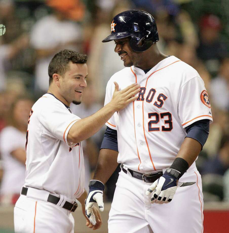 HOUSTON, TX - JUNE 11:  Chris Carter #23 of the Houston Astros is congrtaulatred by Jose Altuve #27 after hitting his second home run of the game against the Arizona Diamondbacks at Minute Maid Park on June 11, 2014 in Houston, Texas. Photo: Bob Levey, Getty Images / 2014 Getty Images